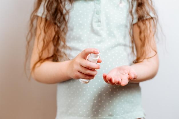 El niño usa un gel antiséptico antibacteriano para desinfectar las manos de las bacterias.