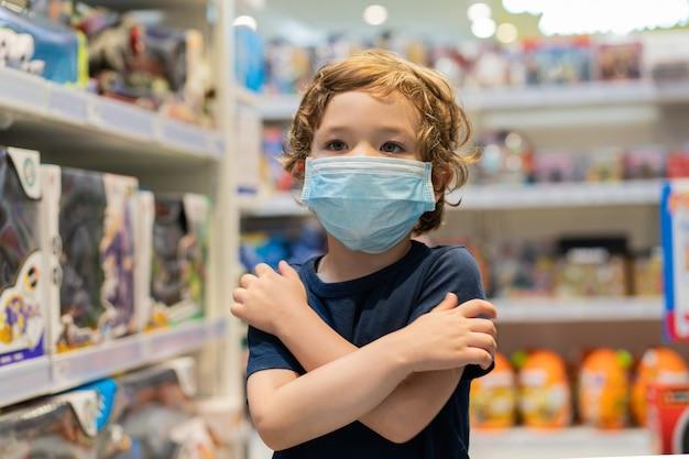 El niño usa una máscara protectora en la tienda. seguridad, protección de la salud durante la cuarentena covid-19.