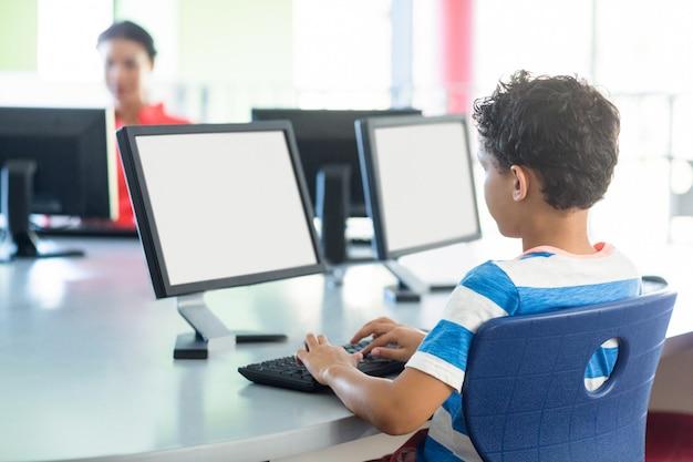 Niño usando computadora contra maestra