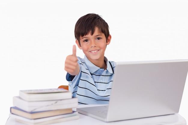 Niño usando una computadora portátil con el pulgar arriba