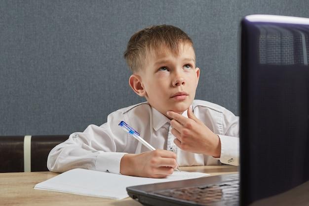 Niño usando una computadora portátil para la tarea