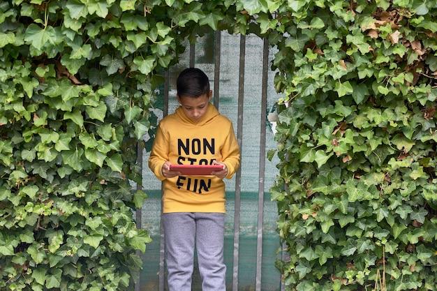 Niño usando su tableta digital en la calle