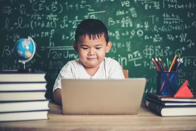 Niño use computadora portátil en el aula.