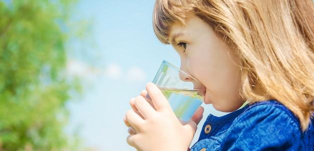 Niño vaso de agua. enfoque selectivo naturaleza.
