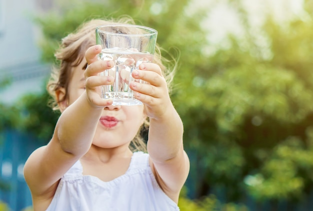 Niño vaso de agua. enfoque selectivo
