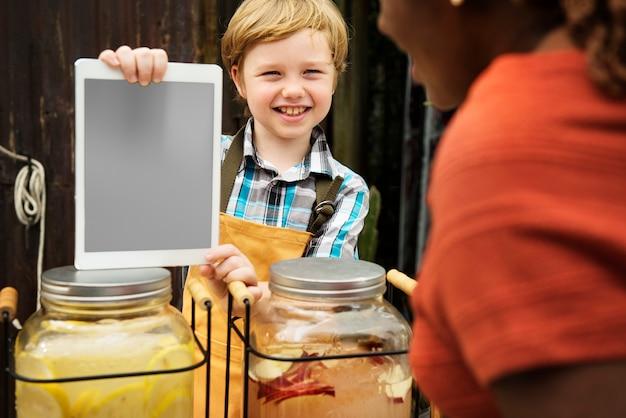 Niño vendiendo jugo de limonada en feria de productos saludables.