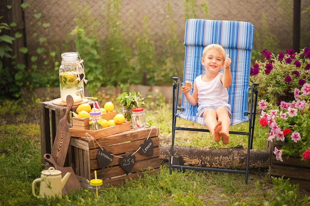 El niño en el verano hace limonada casera.