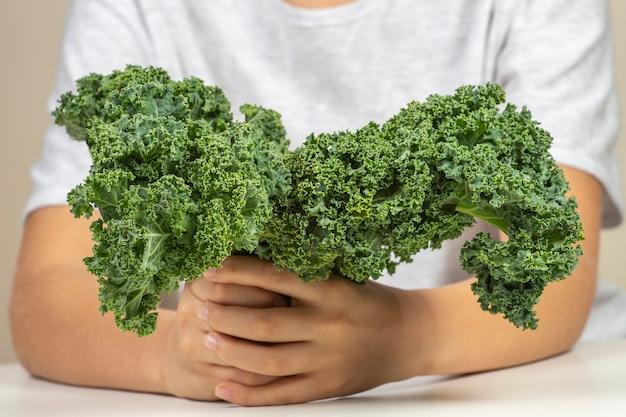 Niño con verduras saludables niño con hojas de col rizada fresca Foto Premium