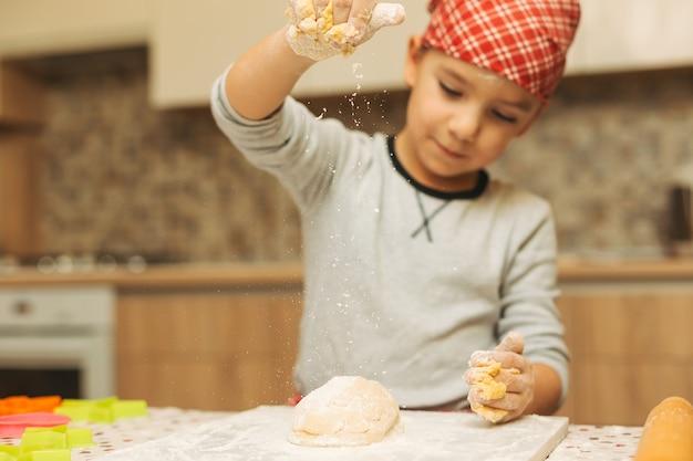 Un niño vertiendo masa con harina.