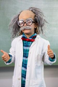Niño vestido como científico gesticulando pulgares arriba signo