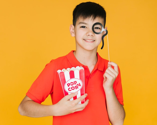 Niño vestido con un monóculo falso con fondo naranja