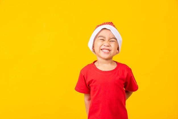 Niño vestido de rojo santa sonríe y entusiasma el concepto de vacaciones el día de navidad