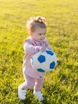 Niño vestido con ropa rosa jugando con pelota