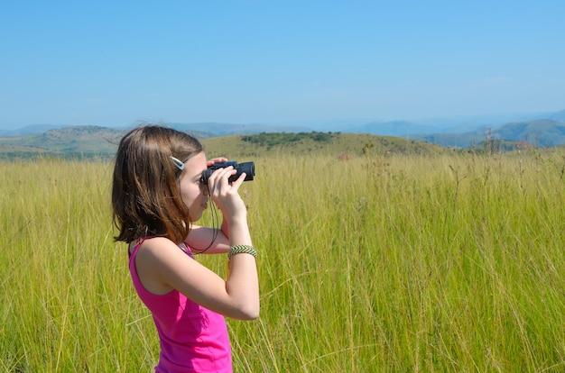 Niño en un viaje de safari en áfrica, niña mirando a la sabana con binoculares