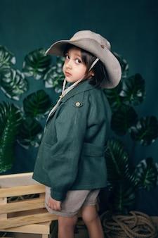 Niño viajero en un sombrero de pie cajas de madera en un estudio sobre un fondo verde