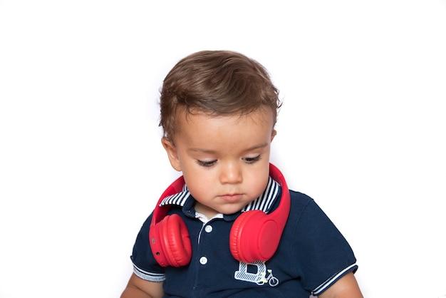 Niño viendo videos en el teléfono móvil con auriculares rojos y camisa azul oscuro
