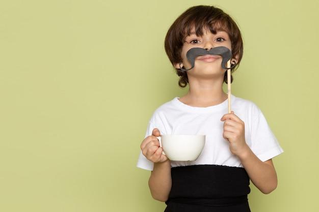 Un niño de vista frontal con bigote y taza de café en camiseta blanca en el piso de color piedra