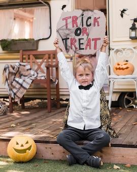 Niño de vista frontal con cartel de truco o trato