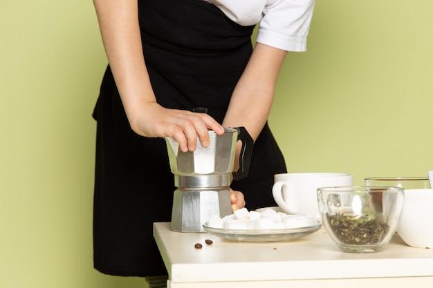 Un niño de vista frontal poco lindo preparar café en camiseta blanca