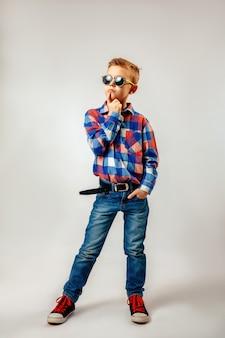 Niño vistiendo camisa a cuadros de colores, blue jeans, gumshoes, gafas de sol, posando y divirtiéndose