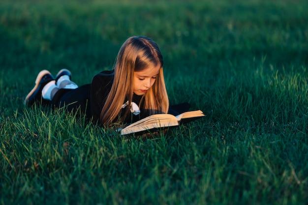 Un niño yace en el césped y lee un libro a la luz del atardecer.