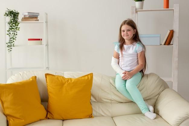 Niño con un yeso en una muñeca o brazo roto sonriendo y divirtiéndose en un sofá. actitud positiva, recuperación y concepto de niño.