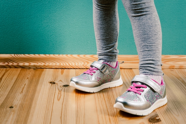 Niño en zapatillas sobre superficie de madera
