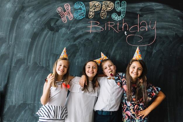 Niños abrazándose cerca de la escritura del feliz cumpleaños