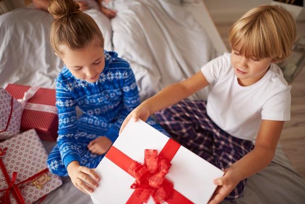 Niños abriendo gran regalo de navidad en la cama.