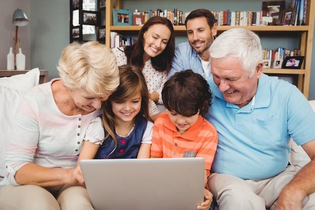 Niños y abuelos sonrientes usando laptop con familia