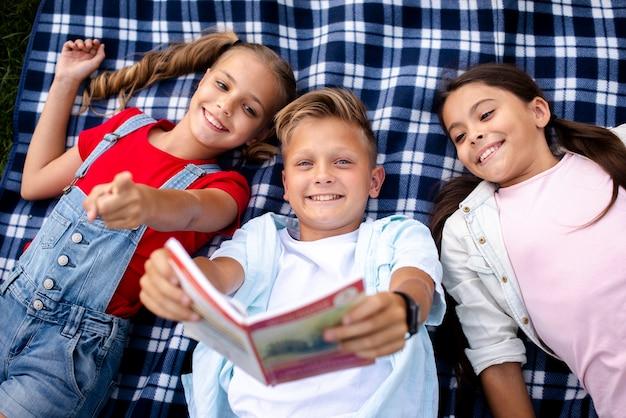 Niños acostados sobre una manta mirando en un libro