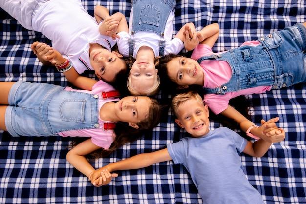 Niños acostados sobre una manta sosteniendo con las manos