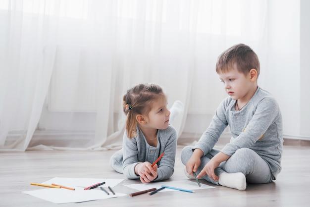 Los niños se acuestan en el piso en pijama y dibujan con lápices. lindo niño pintando con lapices