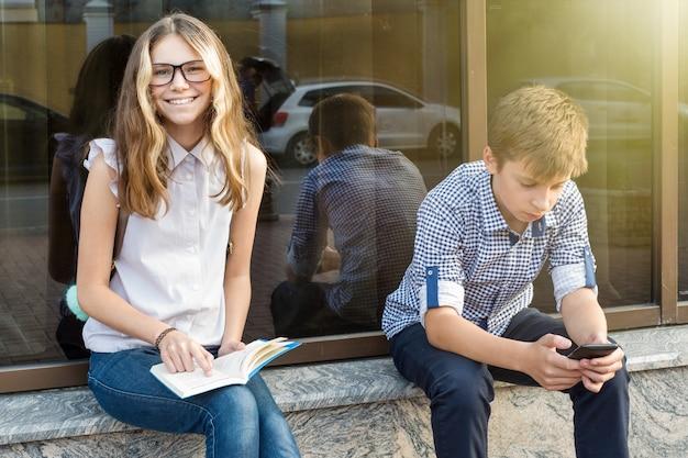 Niños adolescentes, lectura de libros y uso de teléfonos inteligentes.