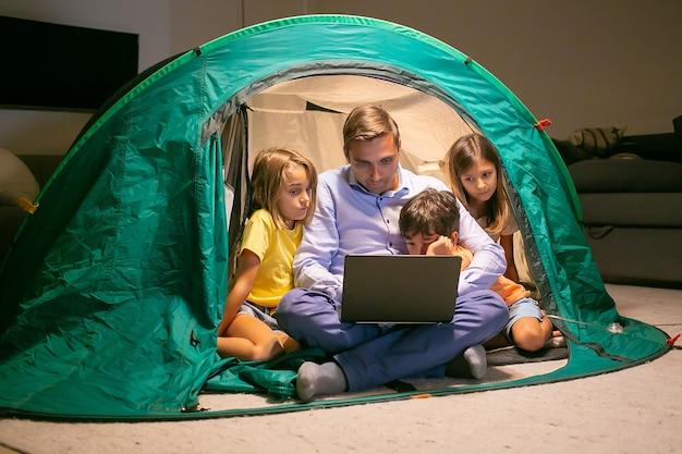 Niños adorables que se relajan con el padre en la tienda de campaña en casa y ven películas en la computadora portátil. niños felices y papá amoroso sentado en la tienda con luz. concepto de infancia, tiempo en familia y fin de semana.