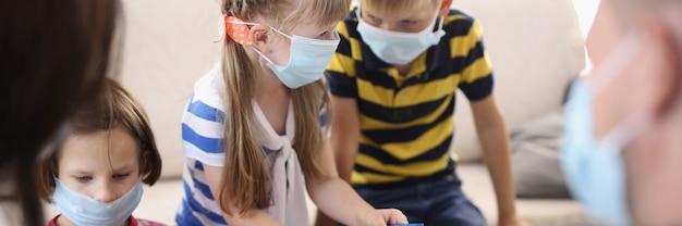 Niños y adultos juegan juegos de mesa con máscaras médicas protectoras.