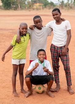 Niños africanos con pelota de fútbol y medalla.