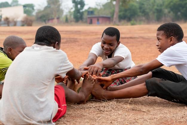 Niños africanos con pelota de fútbol sentado