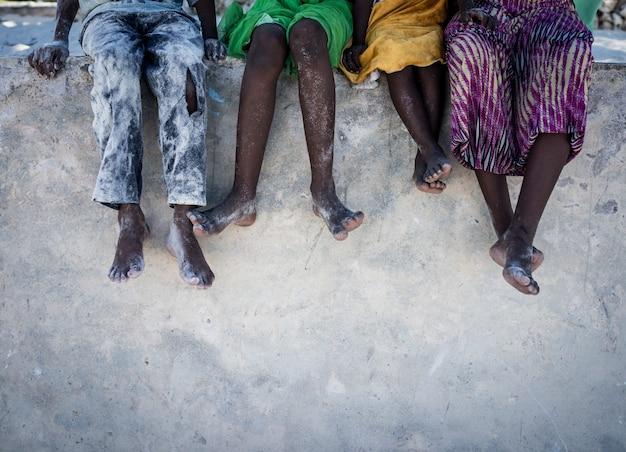 Niños africanos sentados en la pared con los pies hacia abajo