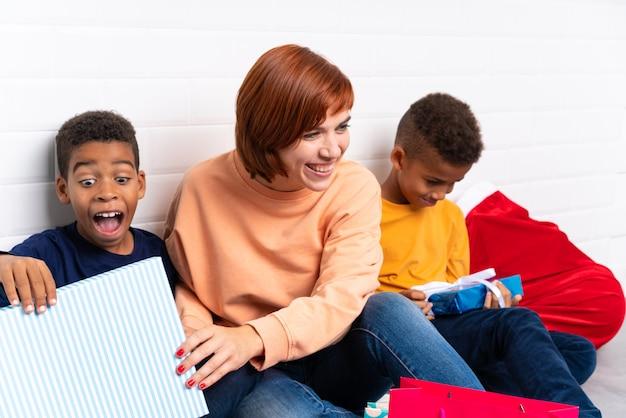 Niños afroamericanos con su madre entre muchos regalos para las fiestas navideñas