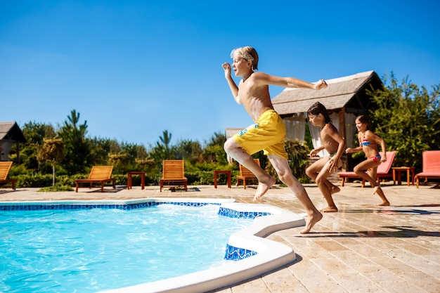 Niños alegres regocijándose, saltando, nadando en la piscina.