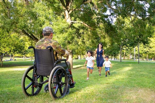 Niños alegres y su mamá se encuentran con un padre militar y corren hacia un hombre discapacitado en camuflaje. veterano de guerra o concepto de regreso a casa