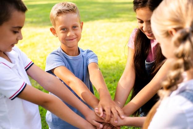 Niños alegres uniendo manos