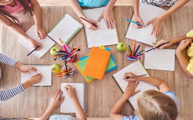 Niños alrededor de la mesa de la escuela.