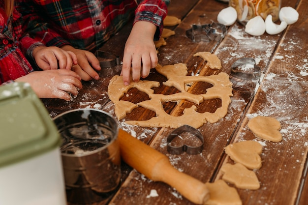 Niños de alto ángulo haciendo galletas juntos en casa