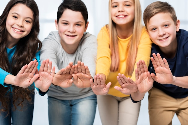 Niños de ángulo bajo mostrando las manos