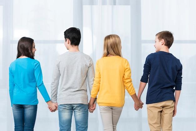 Niños de ángulo bajo tomados de la mano