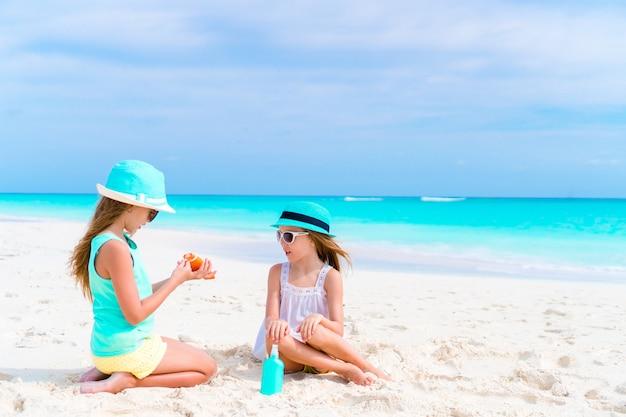 Niños aplicando crema solar entre sí en la playa. el concepto de protección contra la radiación ultravioleta.