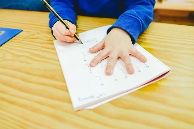 Niños aprendiendo a escribir en el área de alfabetización en una escuela montessori.
