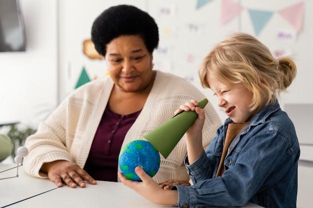 Niños aprendiendo sobre planetas en el aula.